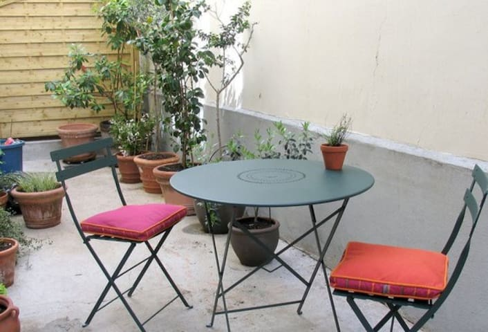 The terrace is furnished with a table and its 2 chairs, concrete floor.