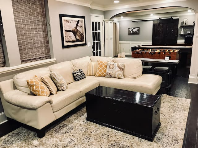 Full entertaining living area with comfortable leather sectional and bar, adjacent to recreation area with pool table and foosball table.