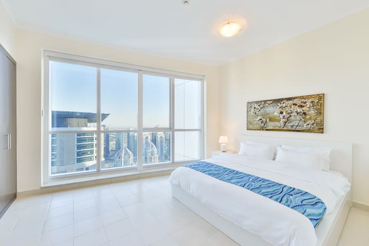 Art decorated second bedroom features a King size bed and floor-to-ceiling windows with electric blackout blinds