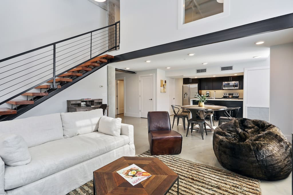 Spacious loft style apartment with floating staircase and stained concrete floors