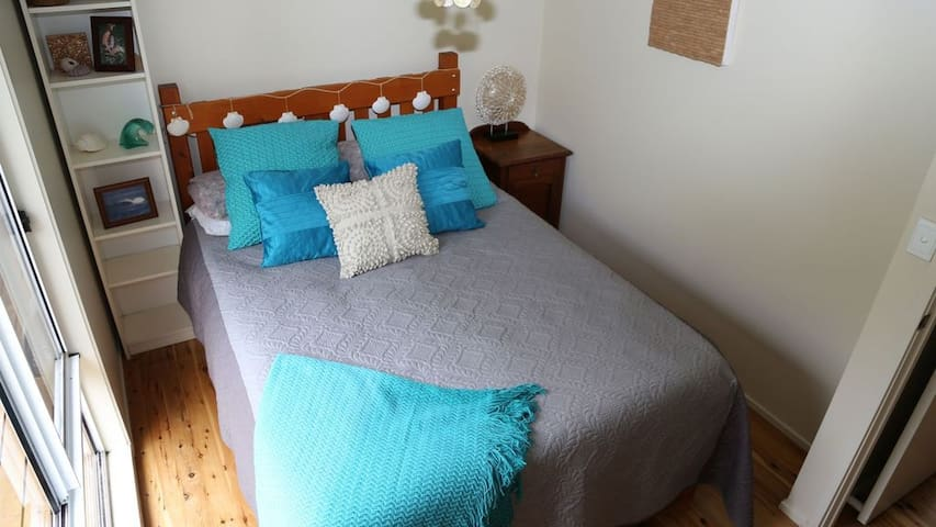 The memory foam topped Queen bed of the second bedroom will have you sleeping in comfort. It overlooks the front deck and private bushland garden.