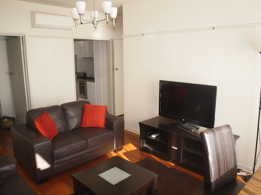 The lounge features comfy couches and a large screen TV, a small dining table with 4 chairs is to right by balcony window