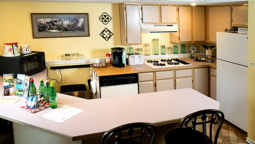 Kitchenette w/ fridge, microwave, stove-top, and coffee maker.
