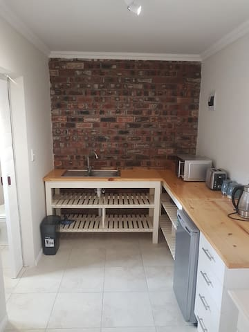 Kitchen area with microwave, toaster, kettle and fridge