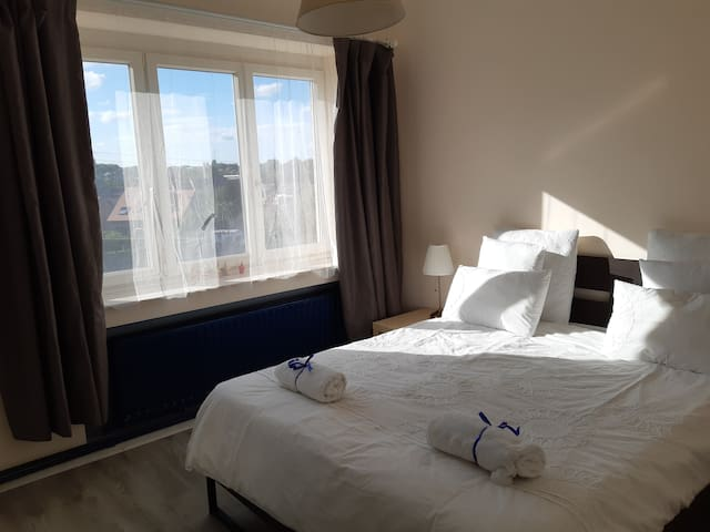 Queen size bed for two view on the city and bright sunshine in the afternoons