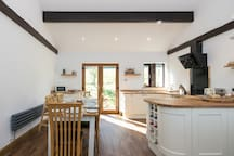 Open plan kitchen / dining area with patio doors leading to the orchard.