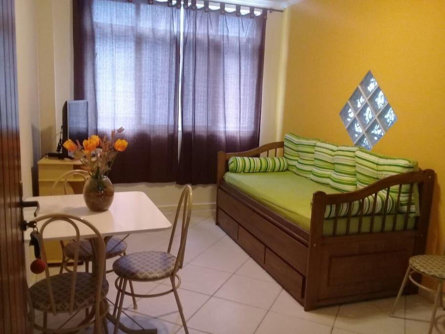Sala com mesa, TV, Bicama/Sofá e ventilador de teto.