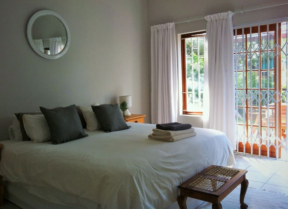 Bedroom opens up with french doors onto a lush and fragrant patio and garden,