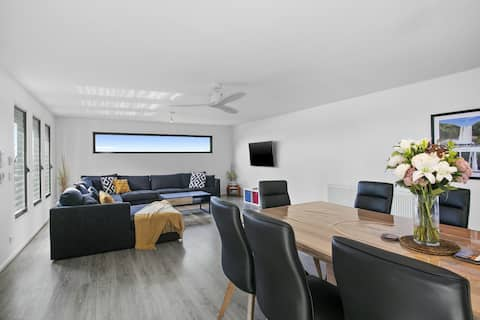 Large open plan living and dining area, with a panoramic window that frames the views from the living room. Designed to be the hub of family life, this area opens onto the deck that enjoys north sunshine and sea air.