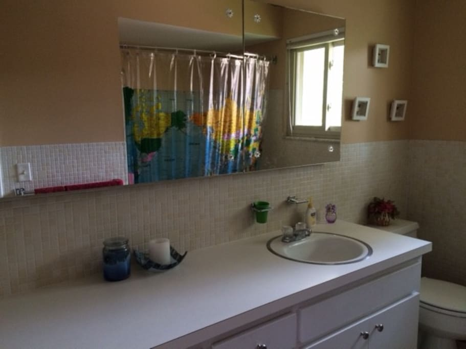 2 sink bathroom. Full size tub with a shower is visible in the mirror