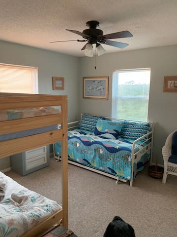 This second floor rear bedroom has a day bed and bunk bed that can accommodate three  younger guests with a pull-out trundle for a fourth. This is the largest bedroom in the house with a great view of the marshland.