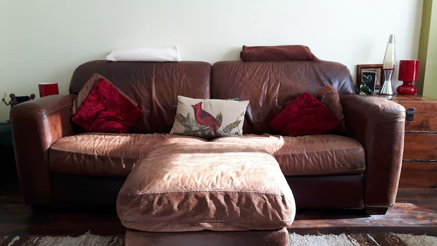 Large comfy main sofa with cushions and blankets