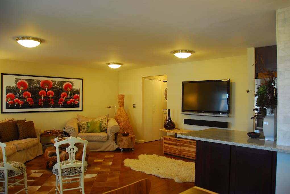 """The living room area , 52"""" TV , free washer and dryer located at the side hallway ,an eat in counter by the side of the kitchen that can be used as a work station or as an eat in counter"""