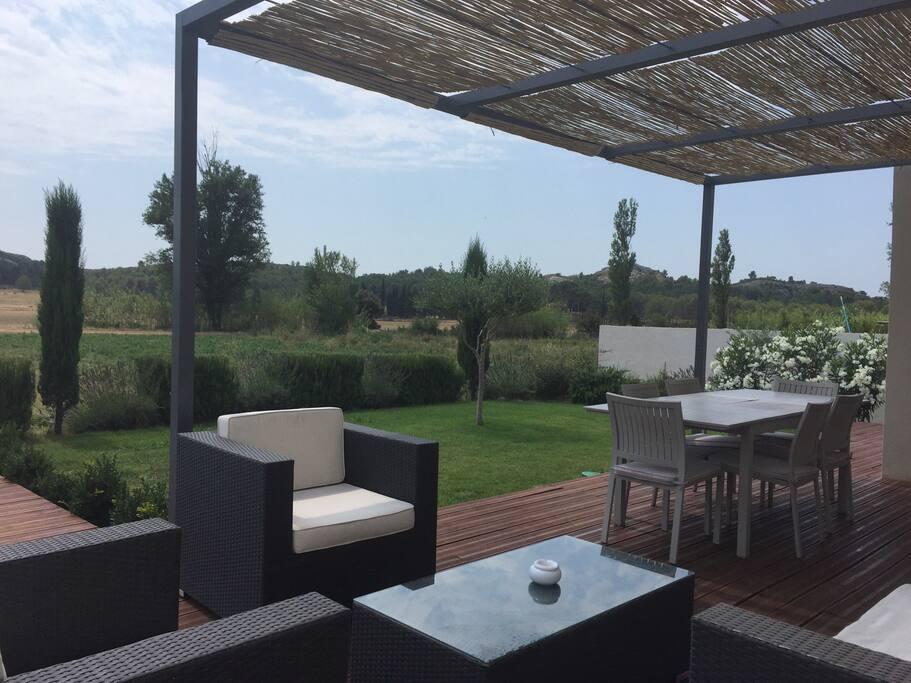 Terrasse ombragée avec son espace repas et petit salon extérieur