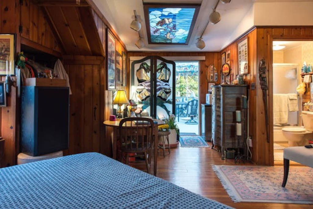 Great golden oak flooring/75 yr old paneling, sky light with glass art and entrance to the deck