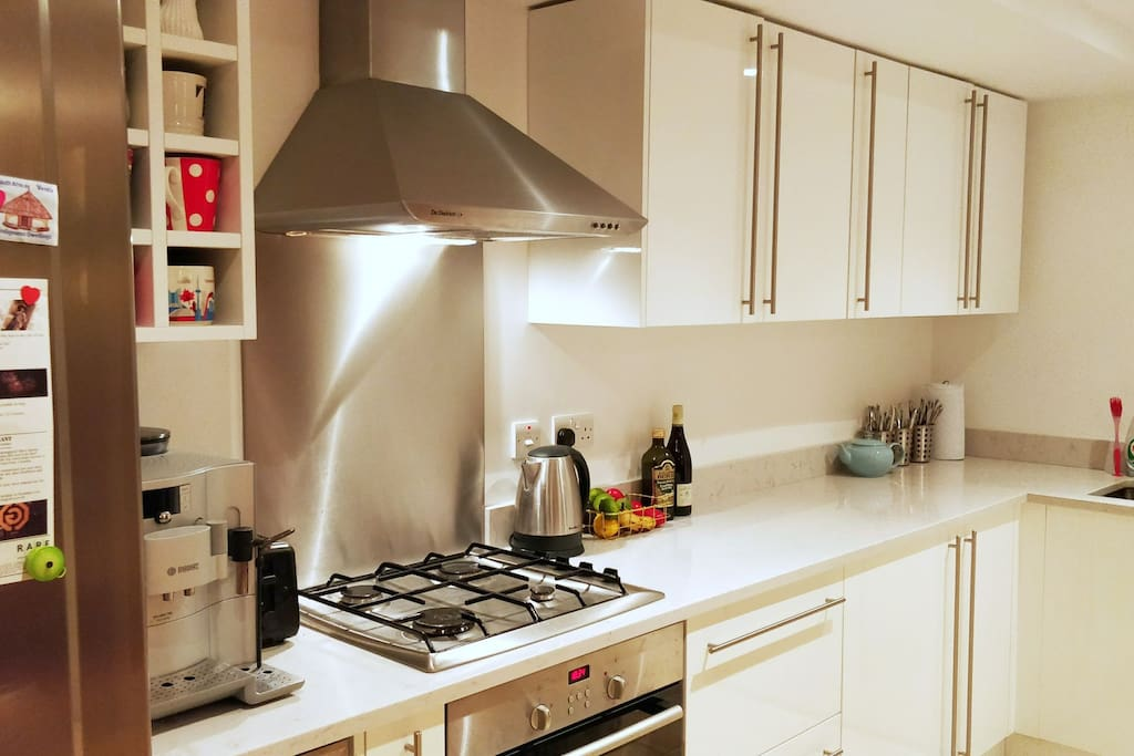 Kitchen with gas stove, wine fridge, and bean to cup espresso machine