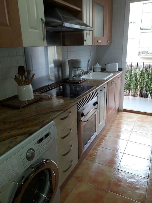 Cocina con vitrocerámica/ inducción y balcón al patio interior. Equipada también con lavadora, lavavajillas, nevera, microondas, tostadora, cafetera y zumera.