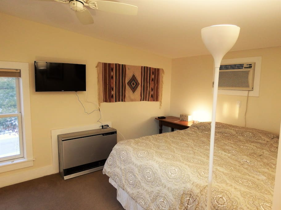Sleeping area with king bed, smart TV on full-motion wall mount so visible in bed or in kitchen