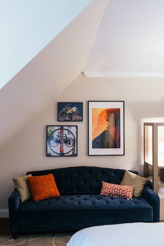 """The Orange Room - Features a Queen sized bed with a 12"""" Memory Foam mattress. It also comes with a couch for additional sleeping space with its own memory foam, an empty closet for your things, and a little sitting area."""