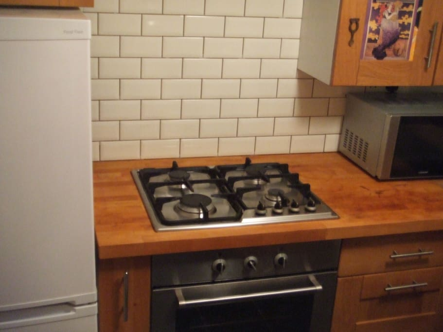 Gas cooker and electric oven, wood counter tops, all nicely tiled.