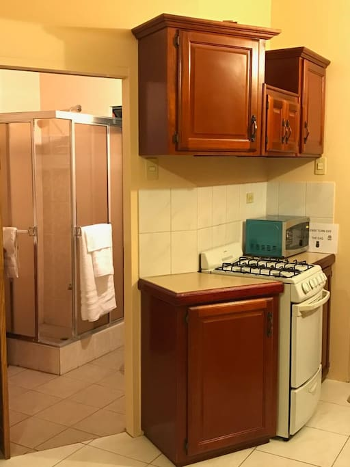 Entrance to bathroom , kitchen area  showing cupboards, stove and microwave