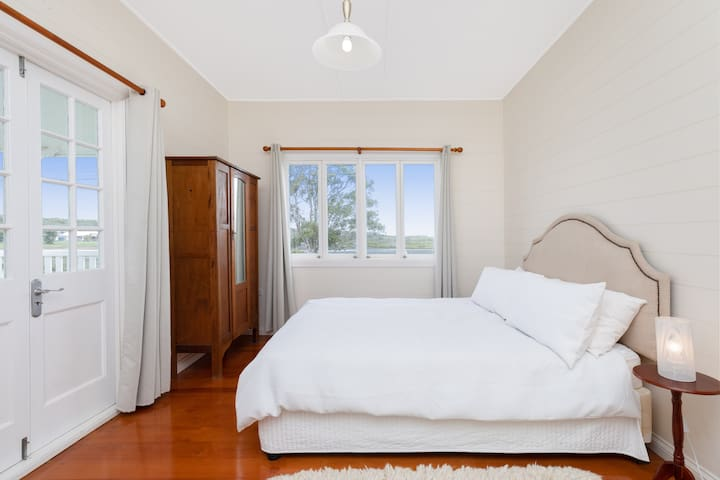 The lovely master bedroom has grand windows allowing natural light to stream through. It has access to the balcony.