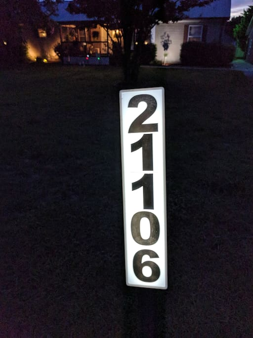 Lighted house number next to the street.