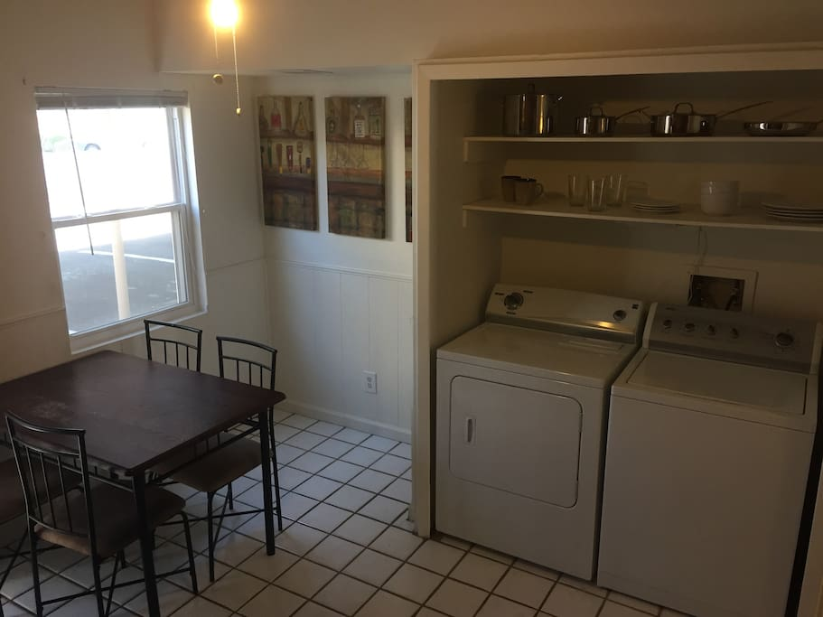 Dinner table, exposed dishes and full size washer and dryer.