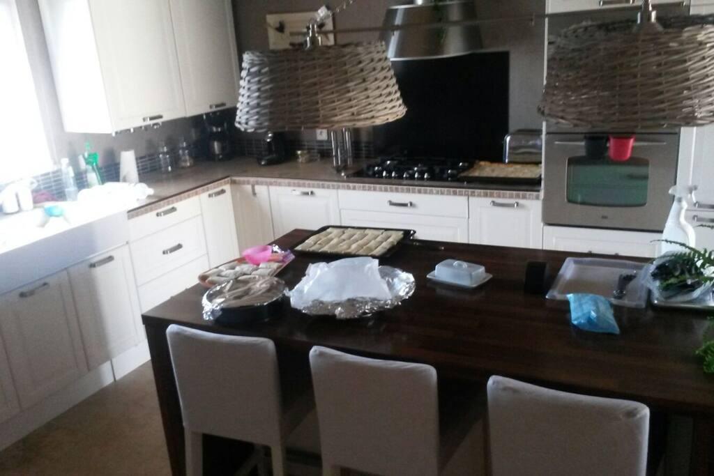 grande cuisine avec un ilot centrale et une table accueillant  5 personnes