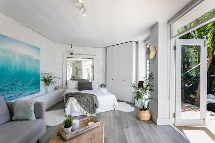 A very comfortable bed, luxury linens, soft plush bathrobes await you. White sandstone walls & double french doors open to a lush backyard. Wardrobe has an iron, ironing board, umbrella, extra blankets, beach bag & towels, & flamingo floaty