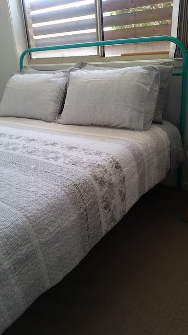 Comfortable queen sized bed with beautiful bedding