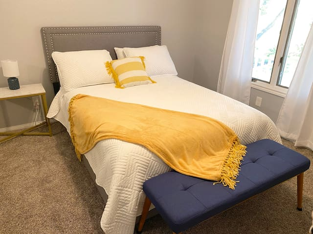 Large room looking onto the front yard with queen bed outfitted with plush comforter and pillows.