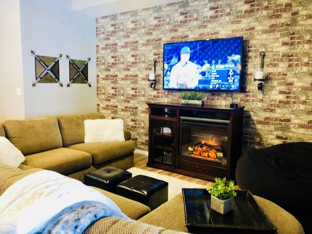 """Living room w/ large sectional, 52"""" TV and electric fireplace. Super comfy/cozy!"""