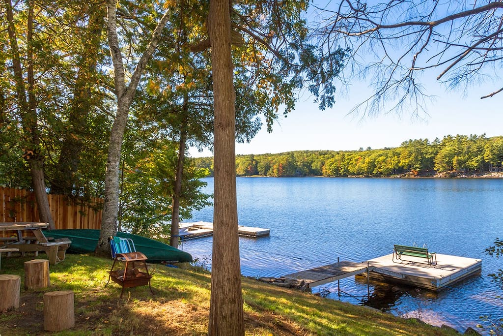 Sloping yard with lounge chairs & firepit. Private dock.