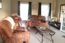 Living Room w/ gas fireplace, piano, couches, wii.