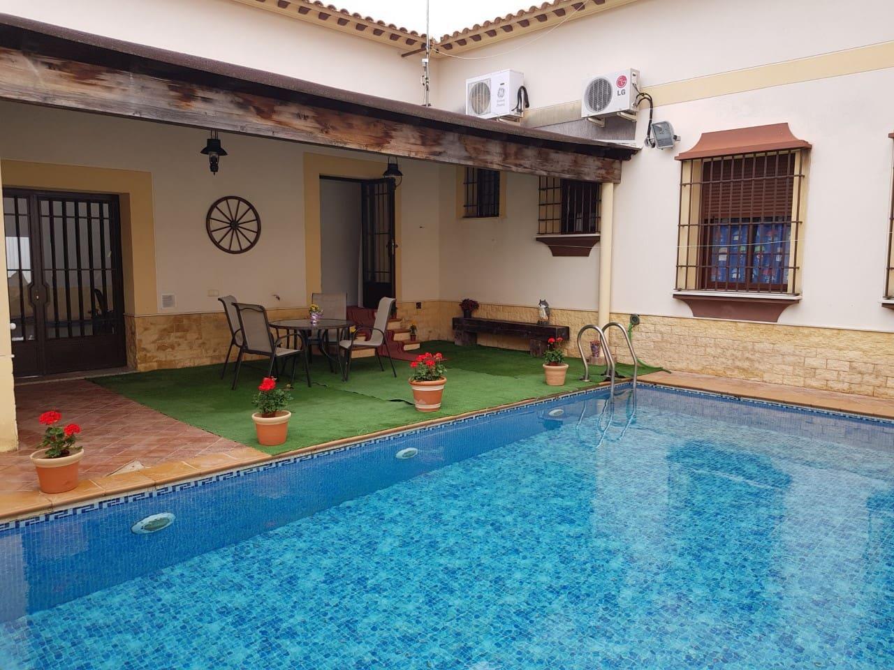 Habitación de matrimonio con baño privado, patio y piscina.