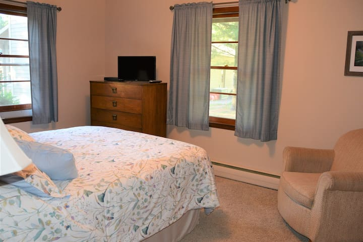Bedroom with queen size bed, dresser, TV and air conditioning.
