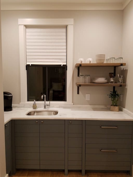 Kitchenette with natural marble countertop, fridge/freezer, Keurig coffee maker, microwave and dishes