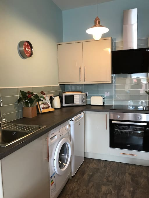 Modern kitchen with hob, oven microwave, washing machine and all  pots pans you need to make a nice meal