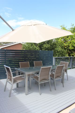 Deck and large shade umbrella. There is also outdoor lighting and a gas bbq.