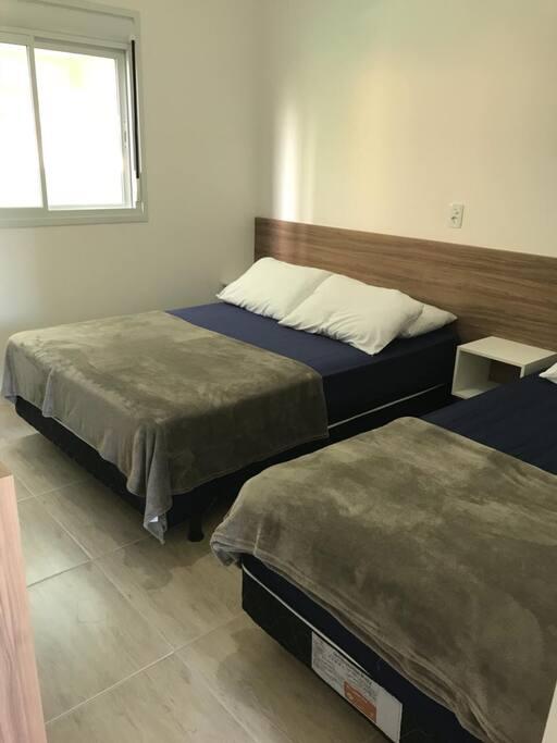 Quarto com uma cama de casal e de solteiro ambas boxes com ar condicionado Wi-Fi.