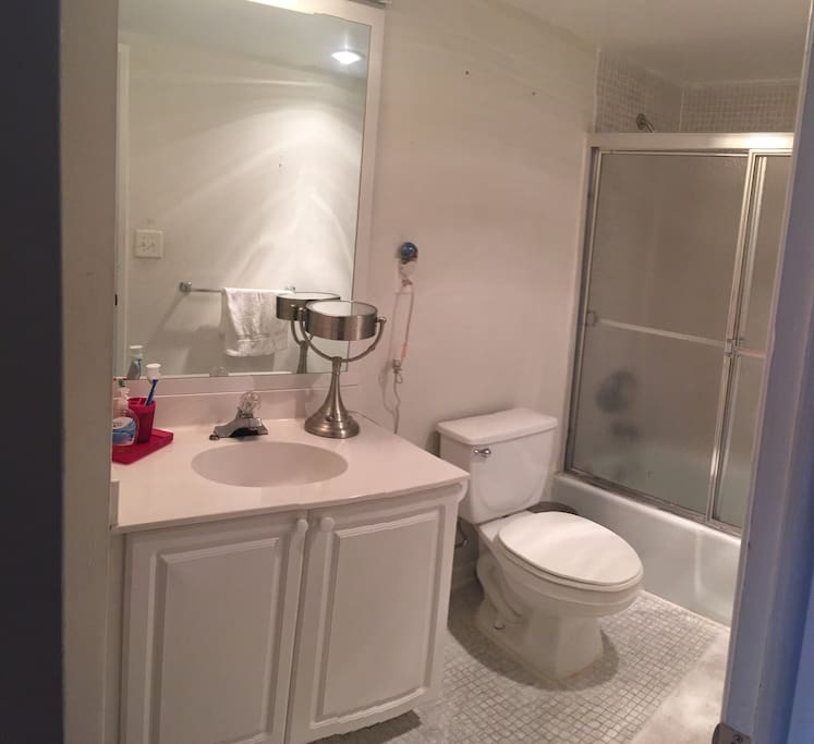 Great bathroom with storage space, bath and shower