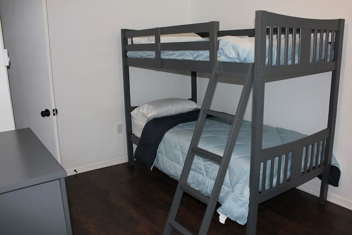 Bunk beds for the kids at heart with dresser and closet.