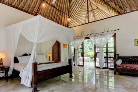 Queen size bed in villa Alami with fresh white cotton linen and mosquito nets