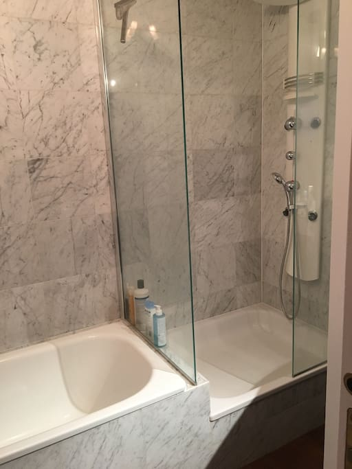 La salle de bain avec douche et baignoire