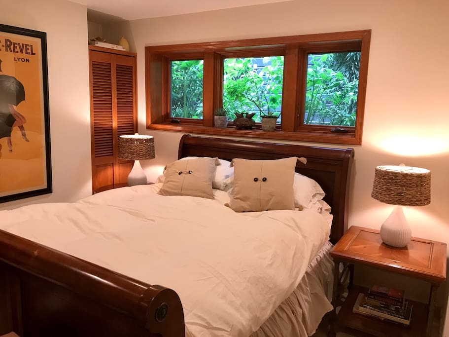 Queen sleigh bed with windows that open to the side garden and sounds of a water feature.
