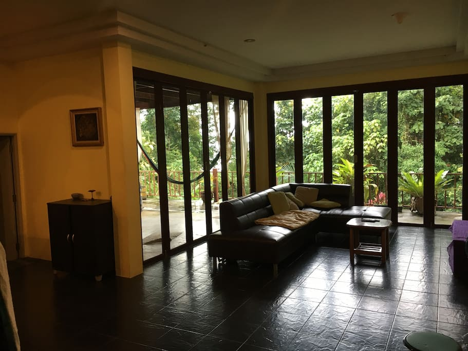 Spacious shared sitting room with large flatscreen T.V,doors open out to hammock seated  chill out terrace and balcony ,surrounding sea and jungle views .