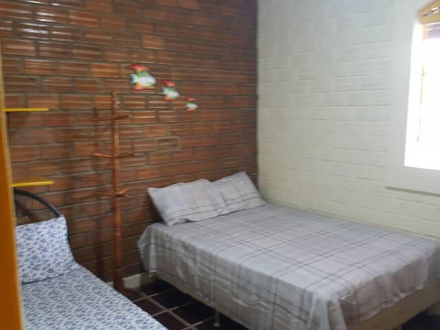 Quarto com 1 cama de casal e 2 de solteiros, este com ventilador.