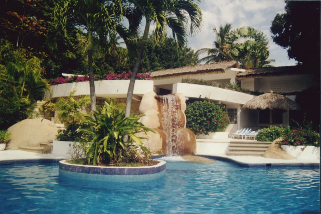 LOWER LEVEL POOL WITH AN ARTIFICIAL CASCADE AND ISLAND WITH TWOO PALM TREES.