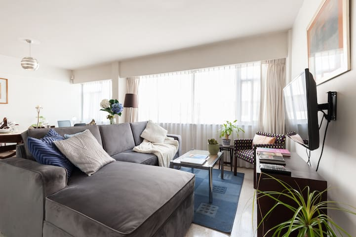 Departamento muy iluminado con Sala muy acogedora, sofá con descansapies de terciopelo gris claro. Cojines para recostarte a descansar o ver la TV solo o sola o en compañía de tu pareja.